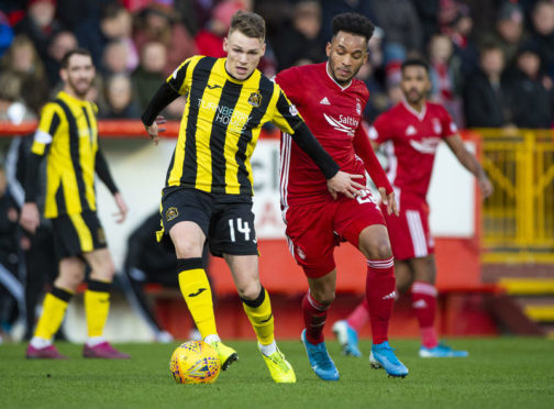 Aberdeen's Funso Ojo and Dumbarton's Joe McKee in action during the William Hill Scottish Cup 4th round tie between Aberdeen and Dumbarton. (Photo by Bill Murray / SNS Group)