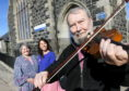 Musician Tom Spiers, with Councillor Anne Stirling and Saskia Gibbon. Picture by Chris Sumner.