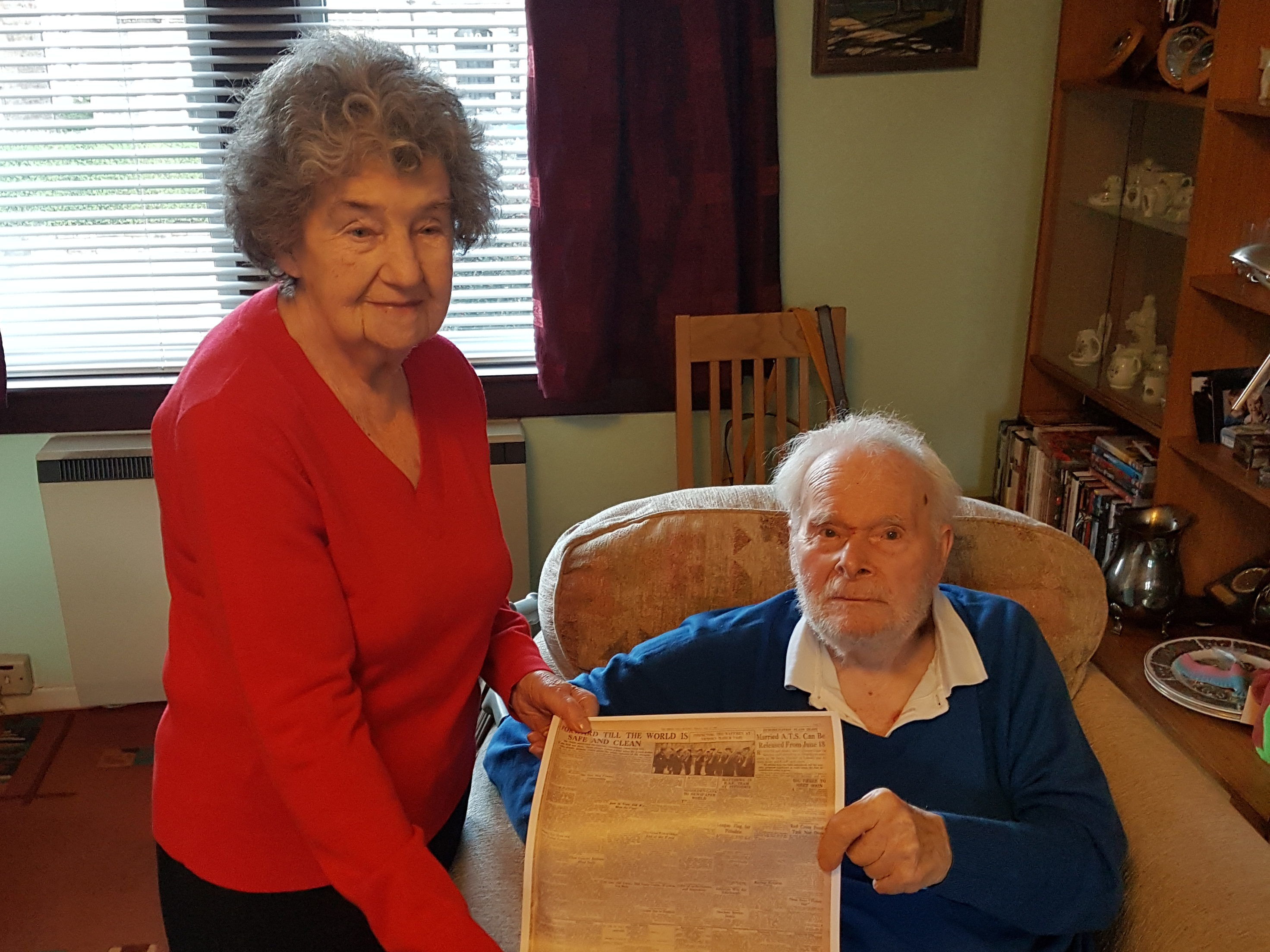 Ronald Halliday and his wife Mary holding a copy of The P&J's coverage of a VE Day parade in 1945