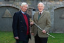 Former lord lieutenant Grenville Johnston passes the sword of office to new appointee Seymour Monro.