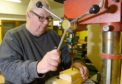 Member Bob Irwin at work on the drill press. Picture by Sandy McCook