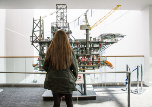 FOI figures show applications for oil and gas courses are making a comeback following a steep drop. Pictured: A student stands in front of a replica of the Alwyn North platform at RGU's Sir Ian Wood building. Credit: RGU.