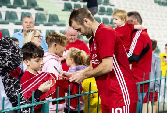 Niall McGinn signs autographs after the friendly with Al Wehdat in Dubai.