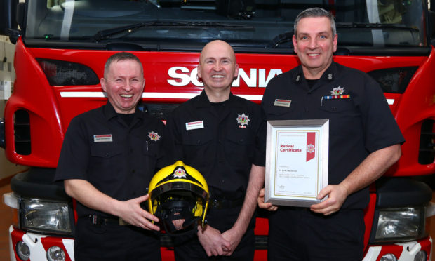 Brian MacDonald, centre, pictured receiving his retirement certificate from his brother John B MacDonald and Oban watch commander Dougie Black.