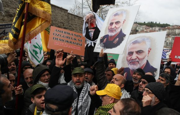 Protesters hold placards showing a portrait of slain Iranian Revolutionary Guards Corps (IRGC) Lieutenant general and commander of the Quds Force Qasem Soleimani and effigy of US President Donald Trump during a demonstration in front of the US consulate in Istanbul, Turkey.