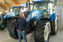 JB Gill beside a line-up of New Holland machinery.