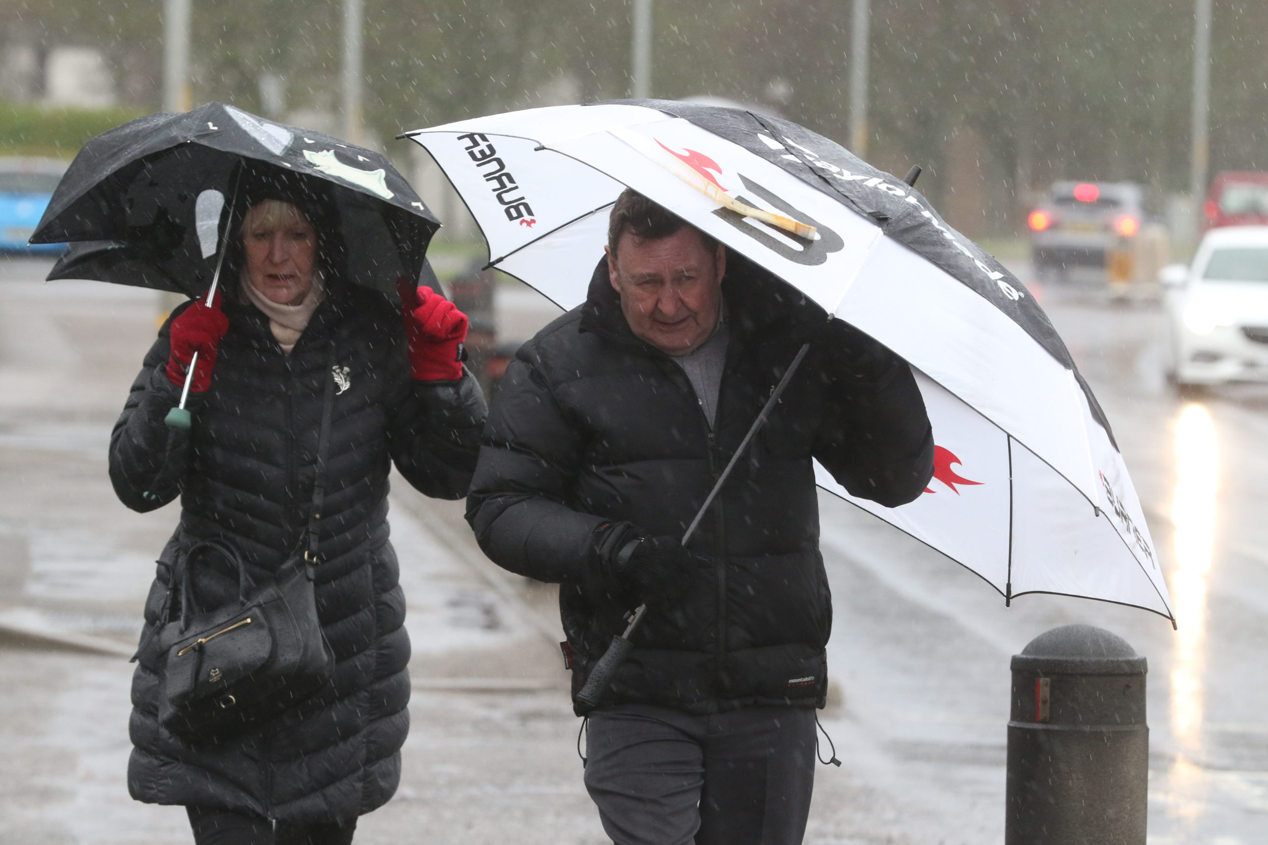 Inverness, UK, 9 February 2020. Two people walk in heavy rain and strong winds on the A96 in Nairn. Credit: Andrew Smith
