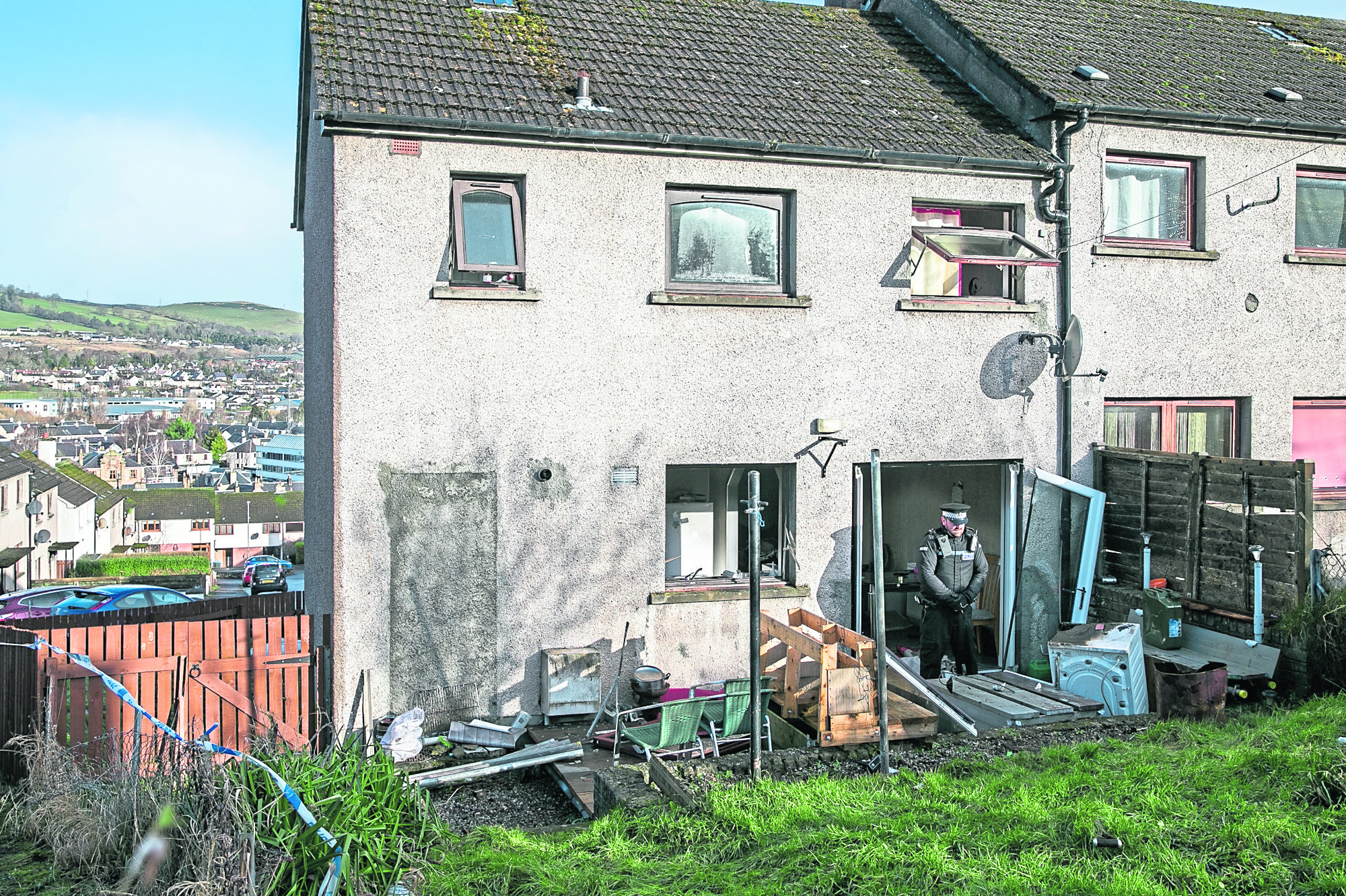 Police maintain a presence at  a house in Dingwall where a suspected small explosion took place hospitalising two.