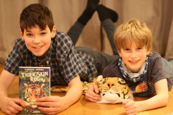 Joan Haig's kids Andrew (11) and Adrian (9) with her novel Tiger Skin Rug.