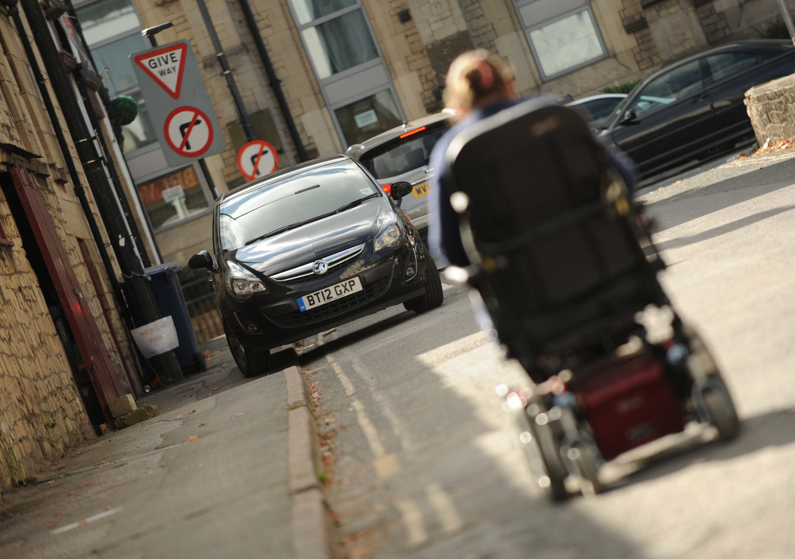 Mandatory Credit: Photo by Paul Gillis/Shutterstock (8556754b) Disabled woman unable to use footpath due to sidewalk parking, car parked on double yellow line. Disabled woman unable to use footpath due to car parked on pavement, UK - 14 Oct 2015