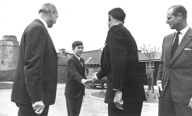Prince Charles shakes hands with his housemaster Robert Whitby, looking on is the Duke and Gordonstoun headmaster Robert Chew.