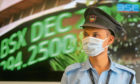 A security guard wearing a mask as a precaution against the new coronavirus stands at the Bombay Stock Exchange (BSE) building in Mumbai, in Mumbai, India, Monday, March 16, 2020. For most people, the new coronavirus causes only mild or moderate symptoms. For some, it can cause more severe illness, especially in older adults and people with existing health problems. (AP Photo/Rafiq Maqbool)