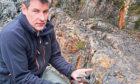 Gavin Berkenheger, managing director of GreenOre Gold, taking rock samples
