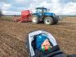 Young Blair Campbell looks on as his dad Scott gets spring crops in the ground.