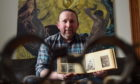 Craig Pithie with his book of mugshots. Photo by Scott Baxter.
