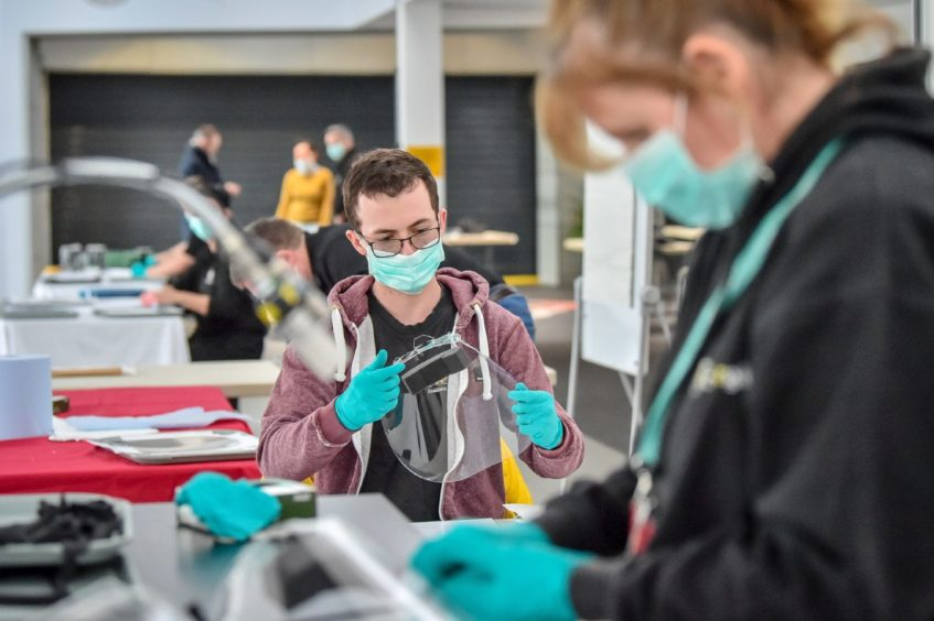 Royal Mint employees assemble full face visors in the cafe inside the Royal Mint Experience.