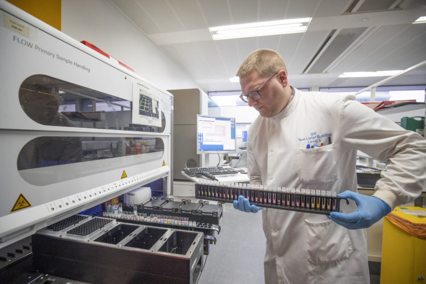 Clinical support technician Douglas Condie extracts viruses from swab samples so that the genetic structure of a virus can be analysed and identified in the coronavirus testing laboratory at Glasgow Royal Infirmary, Glasgow. Picture by Jane Barlow/PA