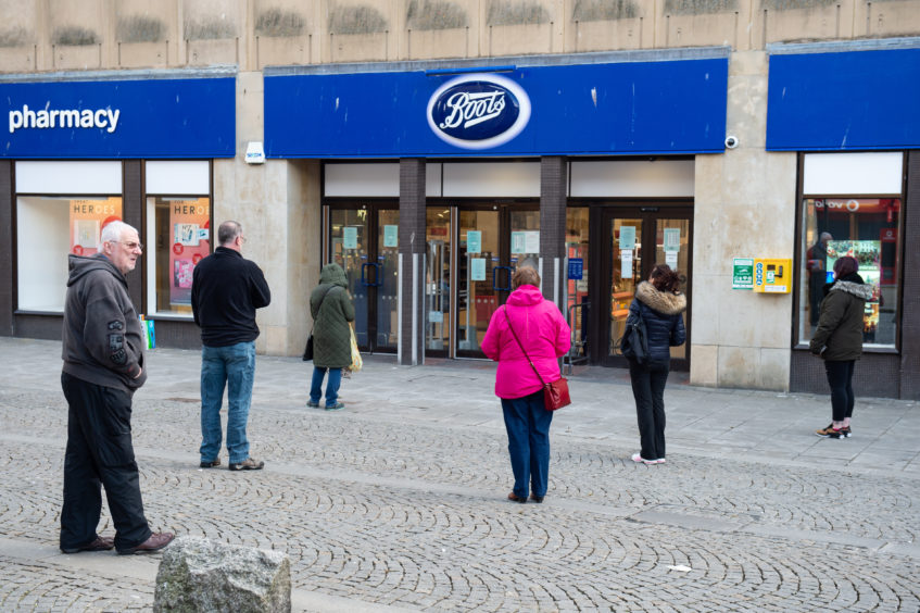 Patients wait outside Boots in Elgin town centre.