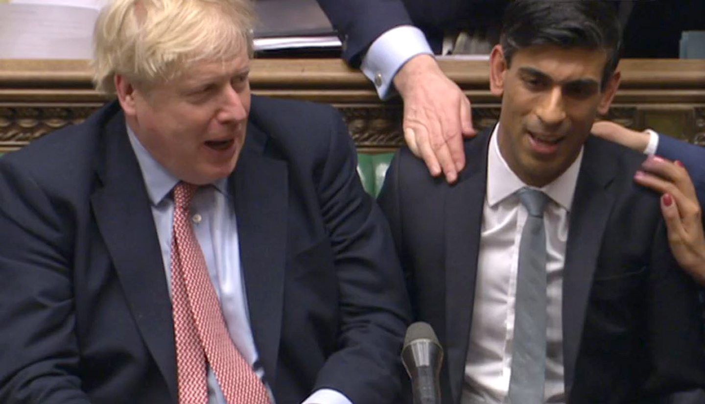 Chancellor Rishi Sunak (right) sits down after delivering his Budget in the House of Commons.
