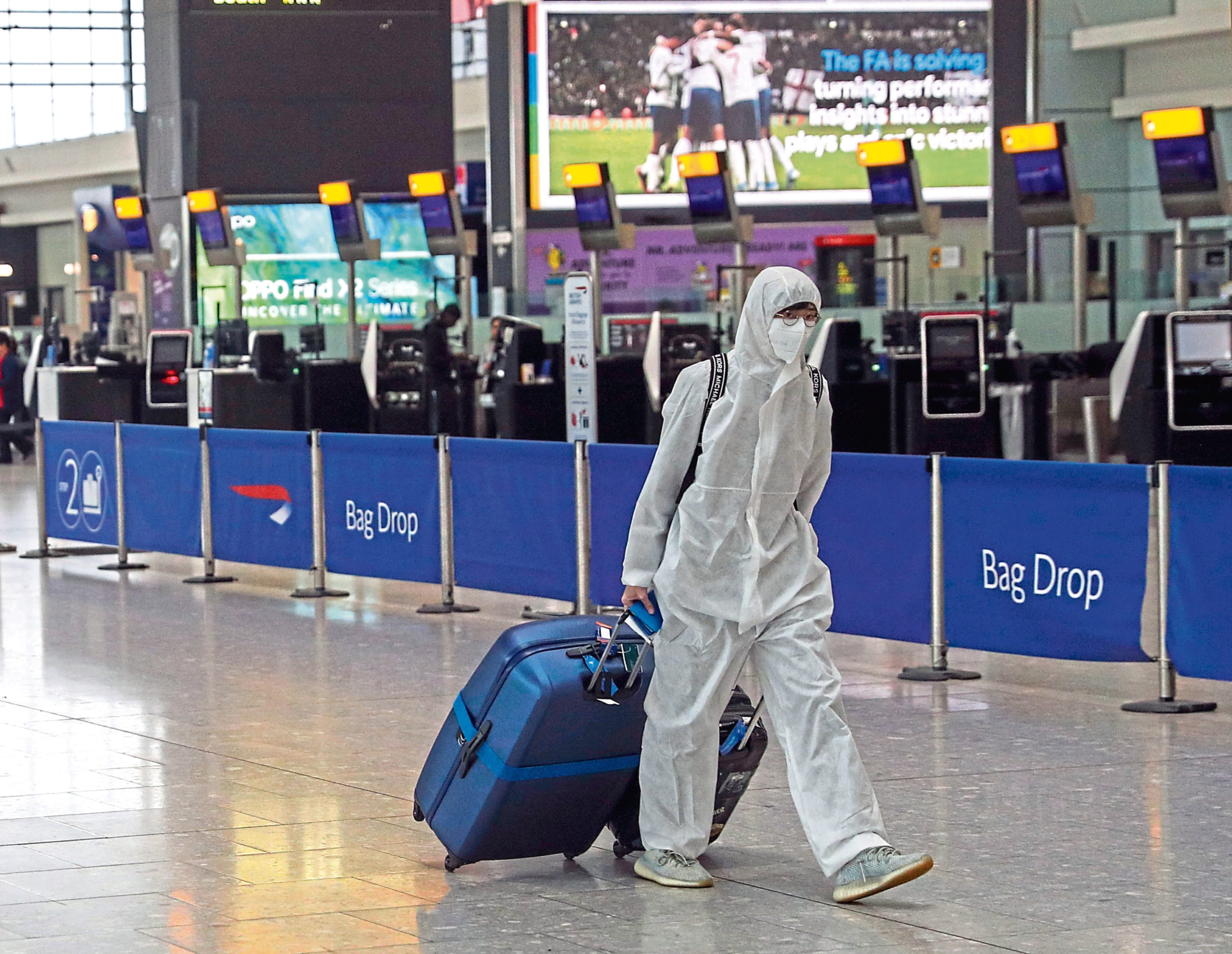 A passenger wearing protective clothing checks in for a flight from Heathrow Airport's Terminal 5 in London. PA Photo. Picture date: Thursday March 19, 2020. See PA story HEALTH Coronavirus. Photo credit should read: Steve Parsons/PA Wire