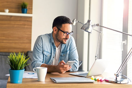 Freelancer working from home and using phone; Shutterstock ID 753395833; Purchase Order: -