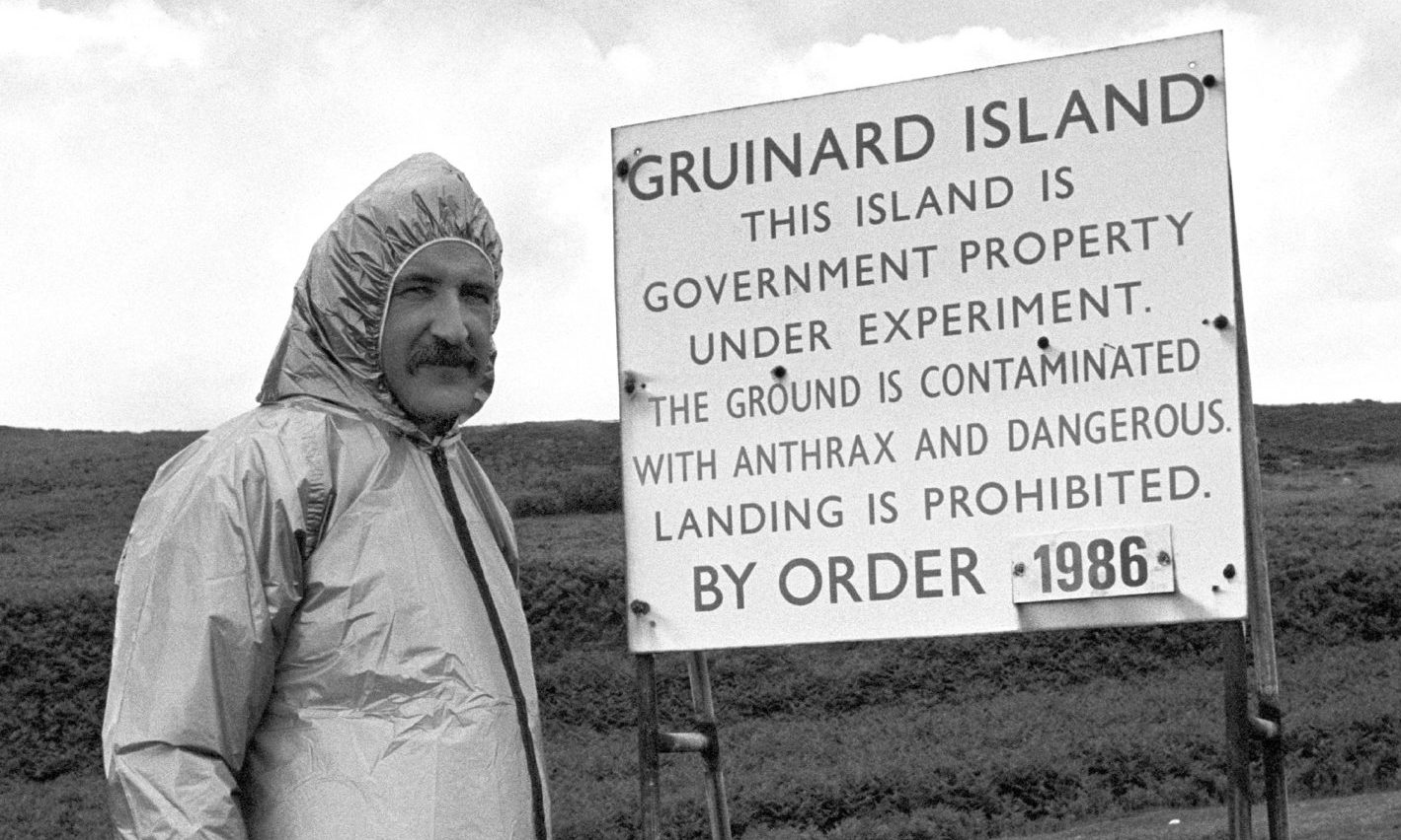 Malcolm Broster of MOD Chemical Defence Establishment at Porton Down, alongside one of the warning signs on the Gruinard Island.