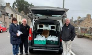 Jessie Mcdougal , trustee Willie Mcdougal and chairman Bill Malcolm out giving food bags.