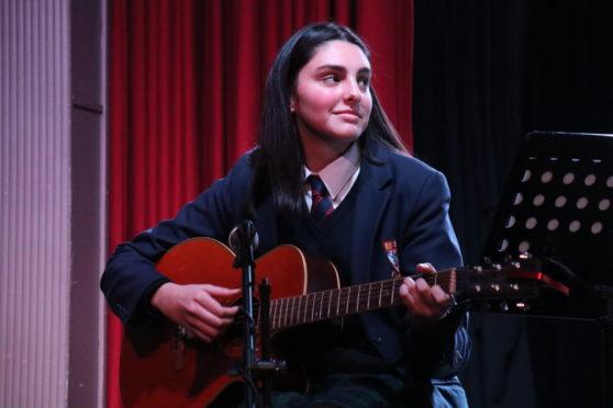 Antonia Saunders playing the guitar.