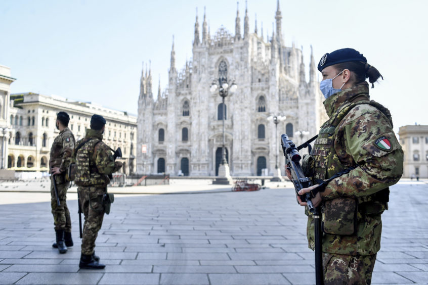 Soldiers patrol in front of the Duomo gothic cathedral in Milan, Italy, Sunday, April 5, 2020.