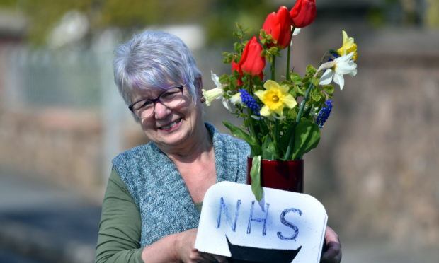 Kathleen Gray from Turriff who along with her husband has been putting out fresh flowers every week in praise of the NHS. Pic by Chris Sumner