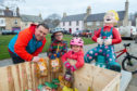Nick, Matthew and Katie Pike collect potatoes from Floo'er Wullie in Fochabers.