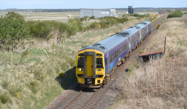 A Scotrail train on the Inverness to Aberdeen line passing the site of the proposed new railway station at Inverness Airport. Picture by Sandy McCook