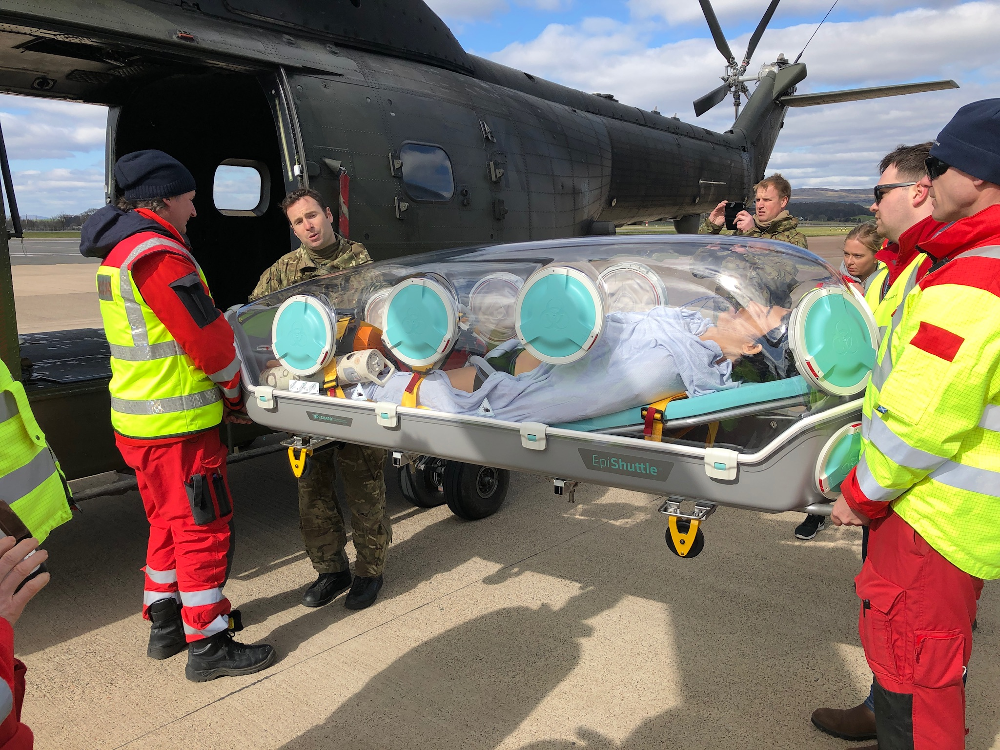 A Puma crewman supports the doctors and Paramedics of the Scottish Ambulance Service during the loading of the EpiShuttle onto the helicopter.