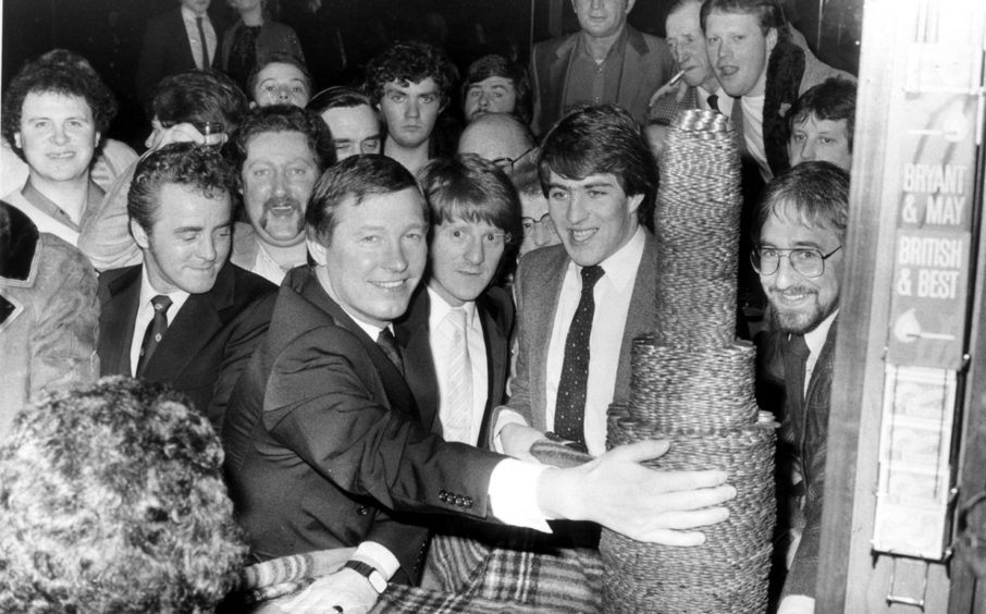 Dons manager Alex Ferguson, midfielder Gordon Strachan and striker Mark McGhee get set to demolish a pile of pennies for charity at the Grampian Bar, Torry,  in 1983. The cash went to the Phoenix Youth Club, Torry.