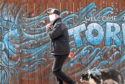A member of the public covers his face with a mask during the Covid-19 lockdown in Torry, Aberdeen. Picture by Kath Flannery.