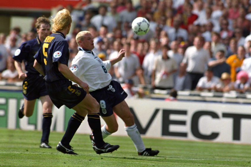 Paul Gascoigne lifts the ball over Colin Hendry en-route to scoring the second for England.