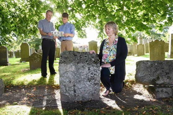 Community councillors Mike Hebenton and Josh MacRae and local resident Elizabeth Barrow with the Pictish Symbol stones at Inverurie Cemetery
