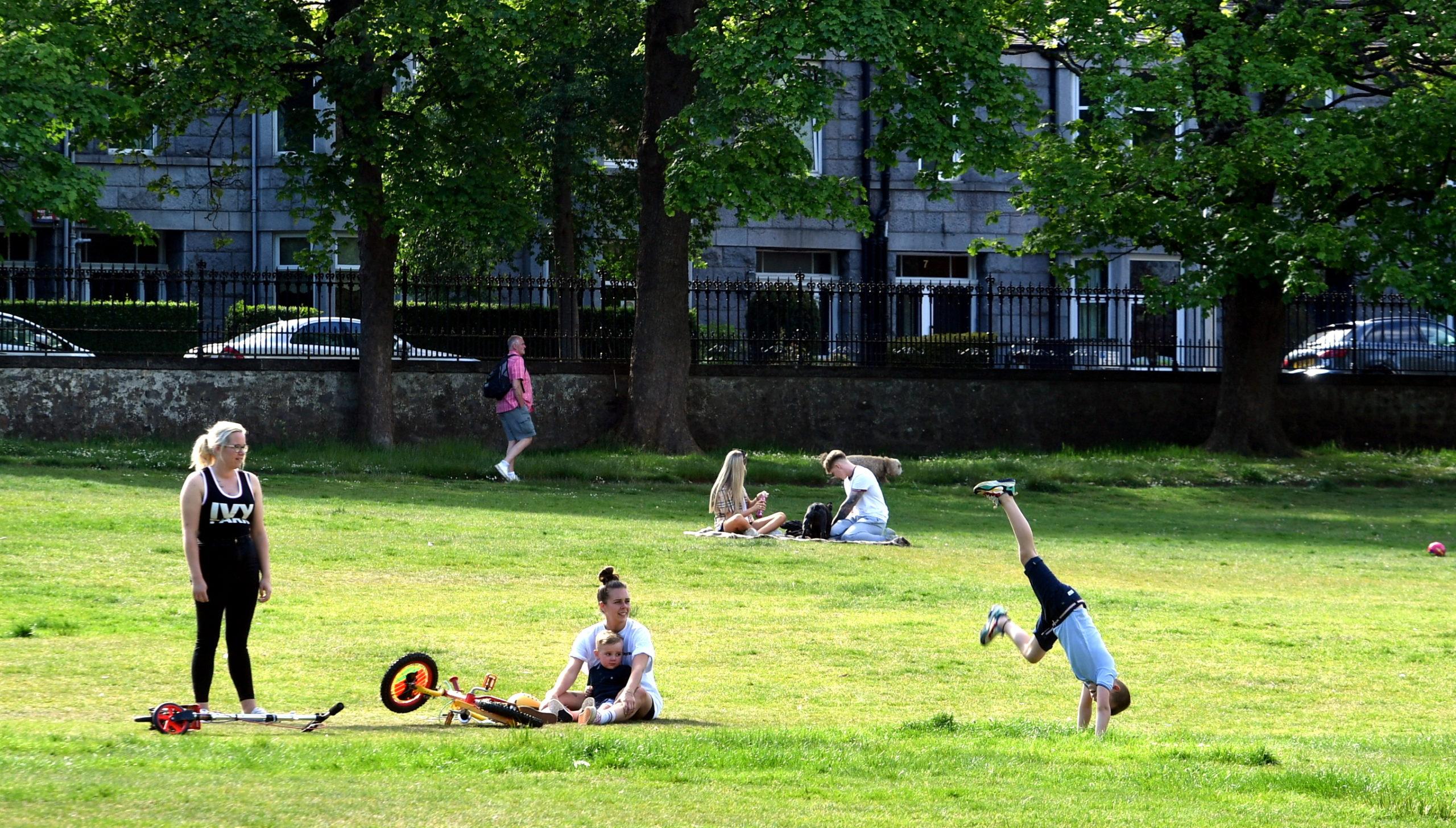People enjoy the weather in Aberdeen's Westburn Park.