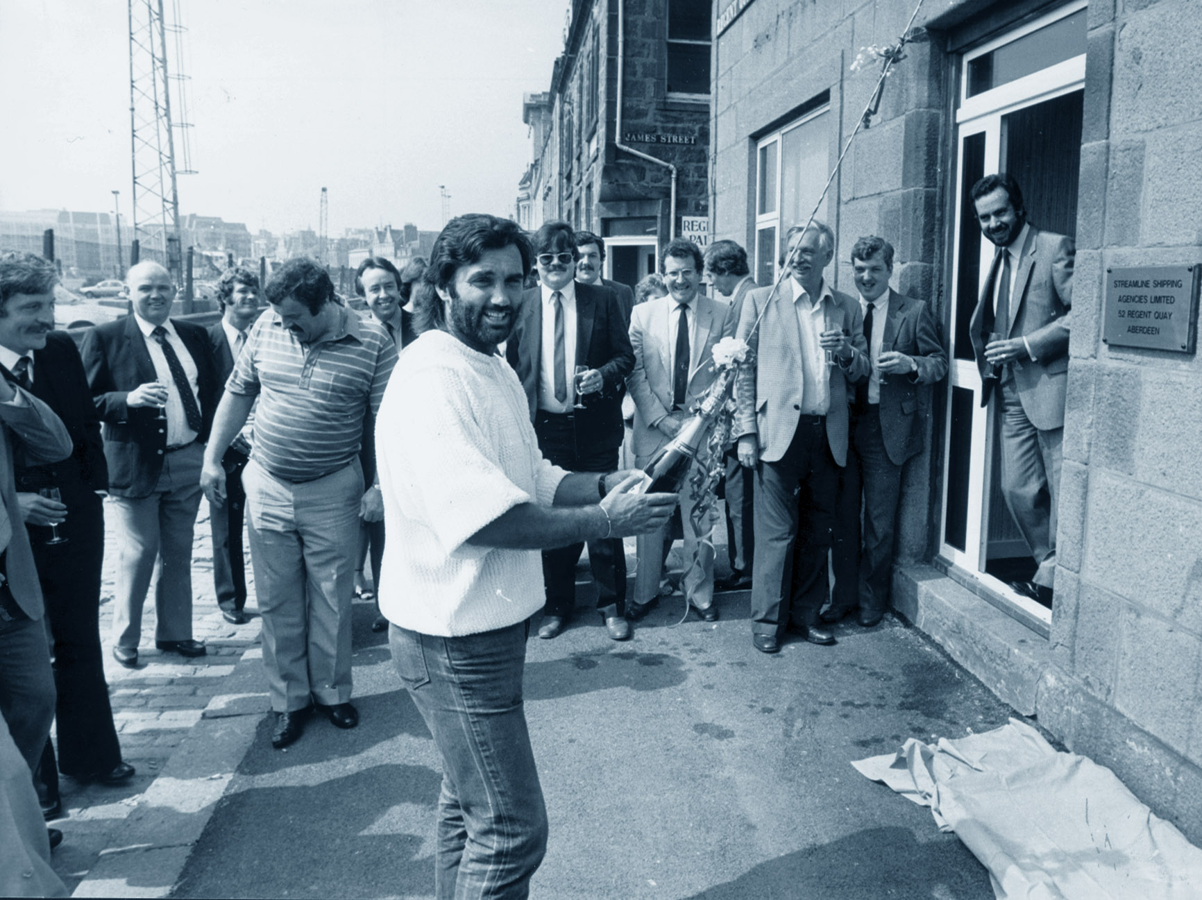George Best about to break open a bottle of champagne to symbolise the opening of new offices for Streamline Shipping Agencies on Regent Quay in 1984.
