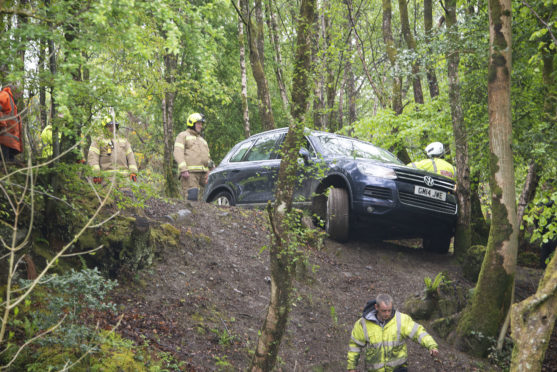 Volkswagen 4x4 hangs over the edge of a 15 foot drop in Fort William after the driver tried to take his car up a steep and winding Forestry Commission footpath.