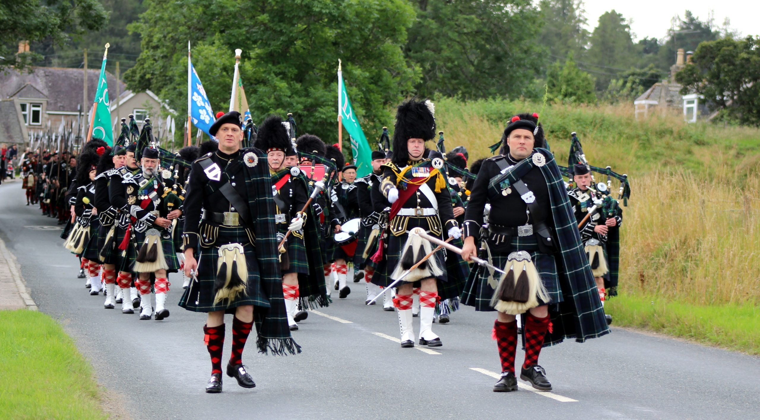 The Lonach Highlanders marching through Bellabeg.