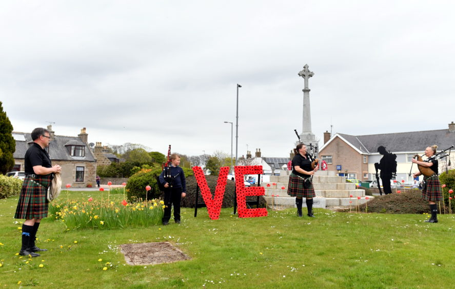CR0021205 Pictured - Four members of the Buchan Peterson Pipe Band play at the Mintlaw war memorial for VE Day, L-R Malcolm Whyte, Kyle Elrick, Pamela Whyte and Mandy Rae.     Picture by Kami Thomson         08-05-2020