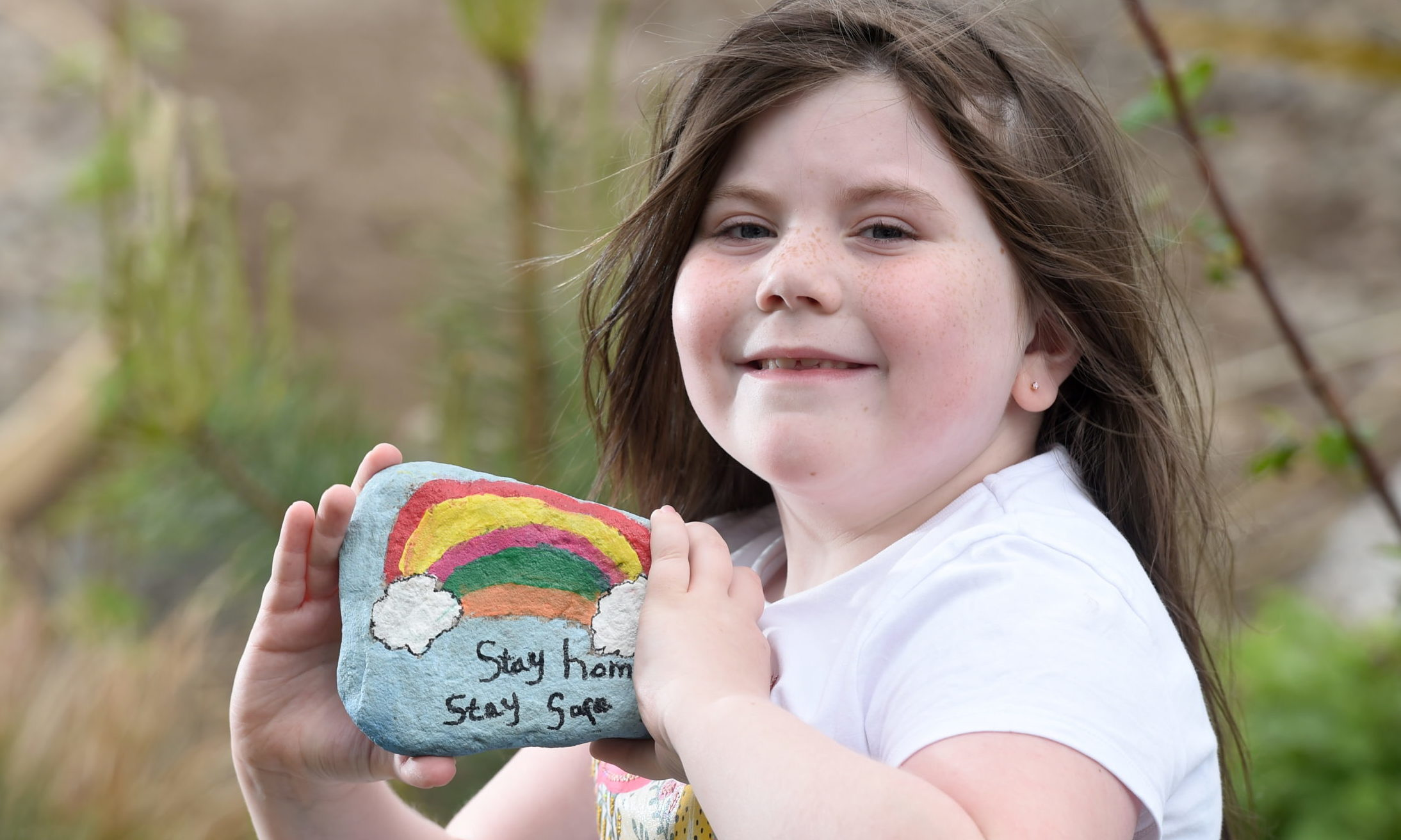 Charlotte Legge in the Natal Gardens , Invergordon with some of their hand painted pebbles. Picture by SANDY McCOOK