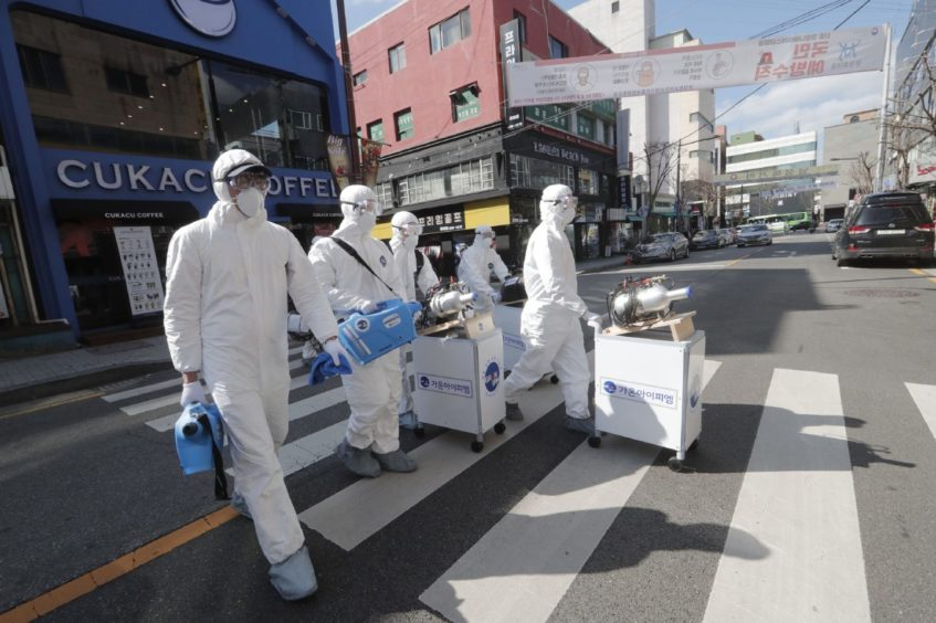 Workers wearing protective gear spray disinfectant as a precaution against the coronavirus in Seoul.