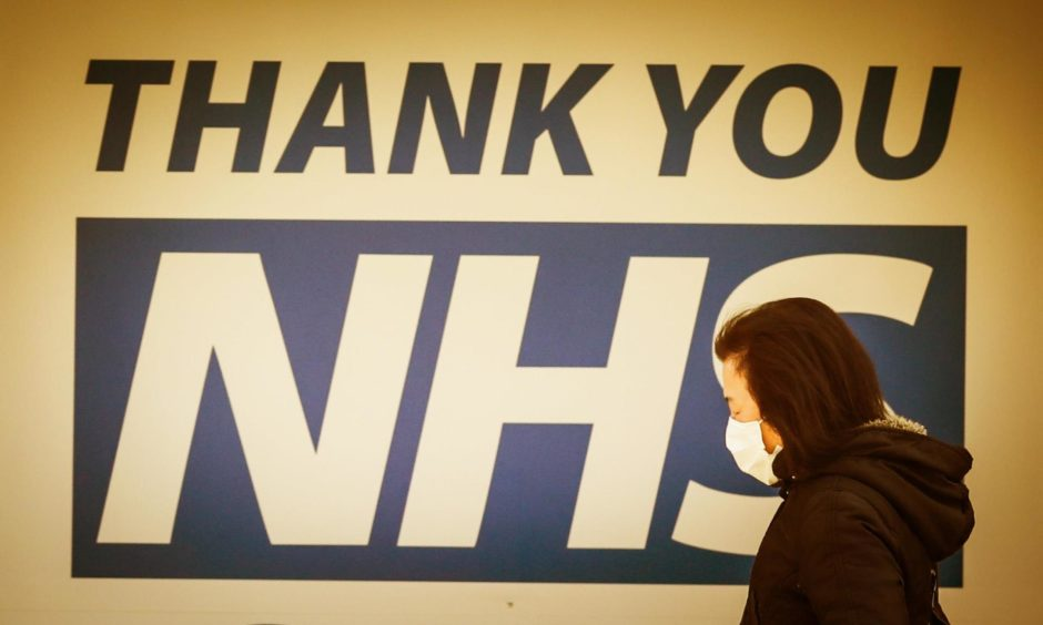 A woman walks past a sign thanking NHS workers.