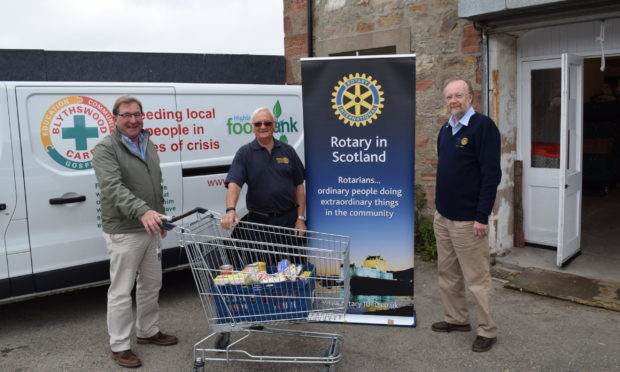 Blythswood chief executive James Campbell is delivered the £1,000 cheque by Mike Halley and Bryan Smith of the Rotary Club of Inverness Loch Ness