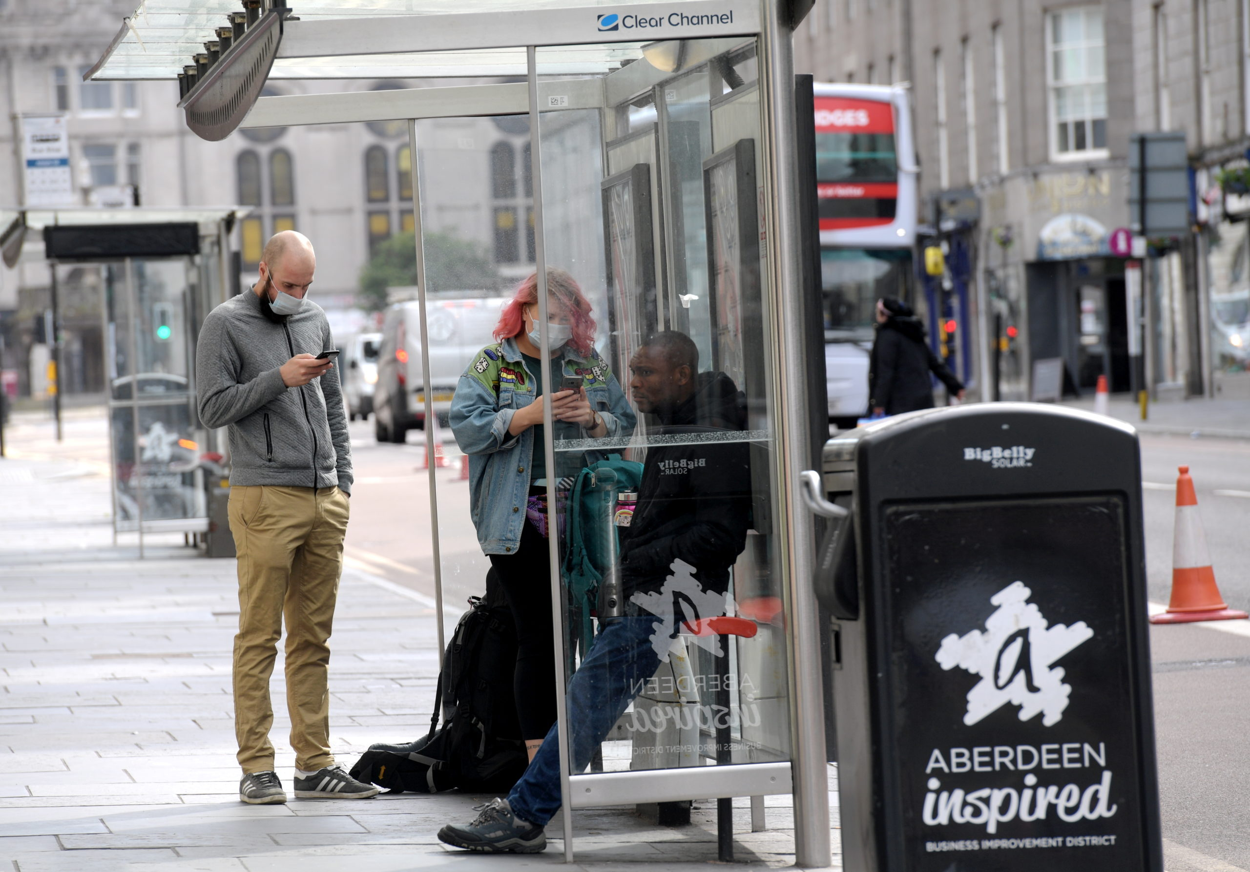 Passengers wear face coverings while waiting for a bus on Aberdeen's Union Street.