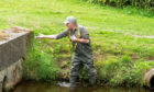 Water Bailiff Alaster Taylor recovers dead fish from the burn.