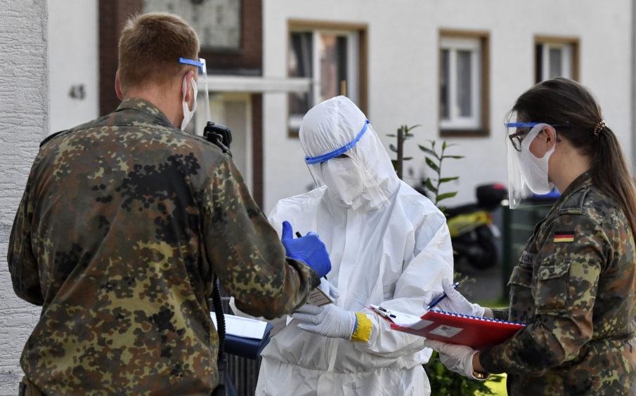 Medical staff and army members take Covid-19 tests of Tonnies employees and their families who are quarantined behind fences in Verl, Germany.