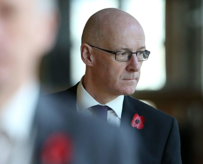 Education secretary John Swinney makes his way to the debating chamber to deliver his statement.